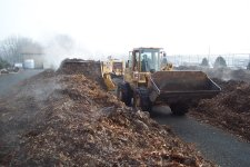 Windrow turner being used to turn leaves to expedite the composting process.