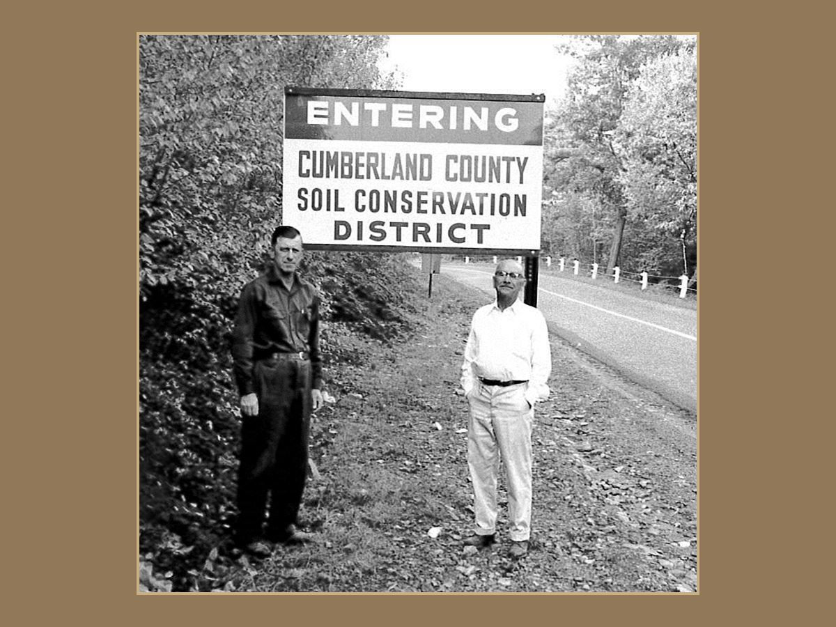 Black and white photo of 2 men standing by Conservation District sign along road